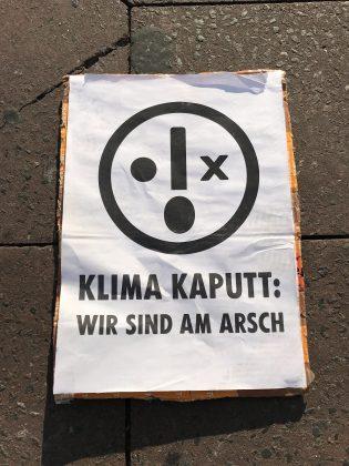 """""""Klima Kaputt: Wir Sind am Arsch"""" steht auf einem der Plakate der Klimaaktivist*innen. Foto: Max Skowronek"""